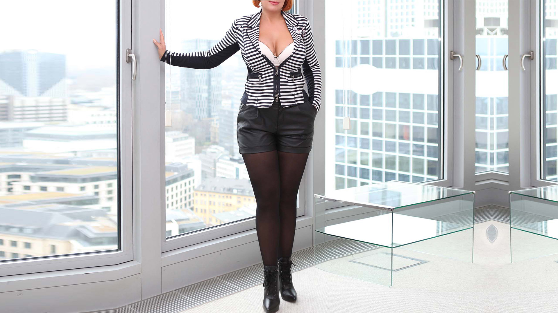 Sofia BBW Escort deluxe in sexy secretary look in shorts and nylons, with a large bust in a wide neckline standing at the window